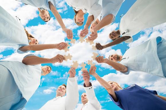 Medical Team Joining Jigsaw Pieces Against Sky