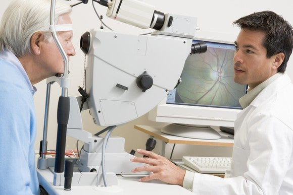 An opthamologist looking at the eyes of an elderly man.