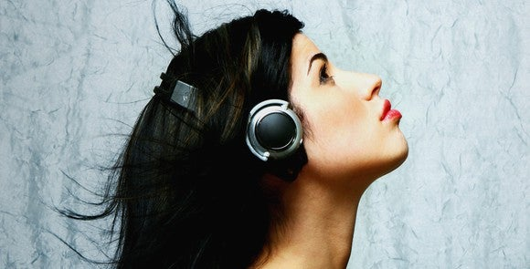 A woman in profile wearing headphones