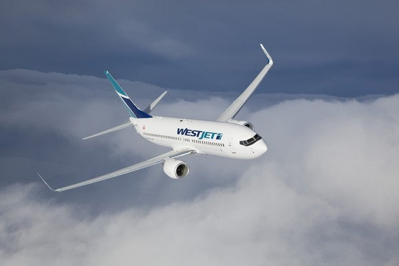 A WestJet plane flying over clouds