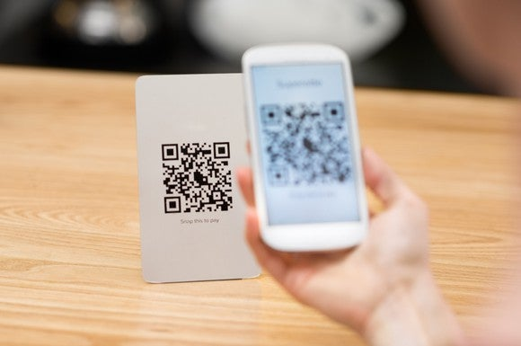 Hand holding a smartphone scanning a QR code.
