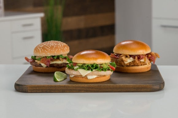 The three new signature artisan sandwiches at McDonald's on a cutting board.