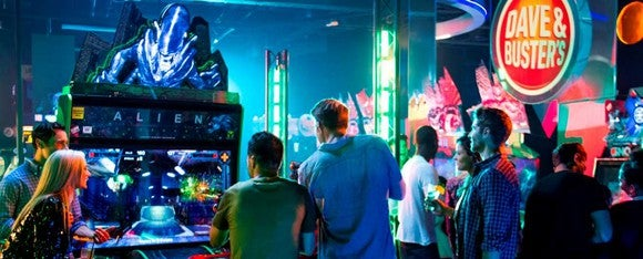 A group of adults gather around the arcade game Alien, based on the popular sci-fi movies, at a Dave and Buster's.