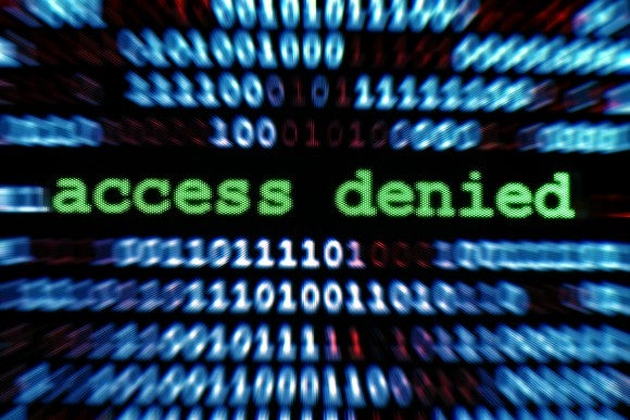 The words access denied on a computer screen, surrounded by binary code.