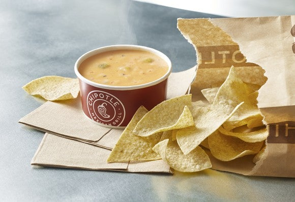 Chipotle Mexican Grill cup of queso with chips spilling out of a bag