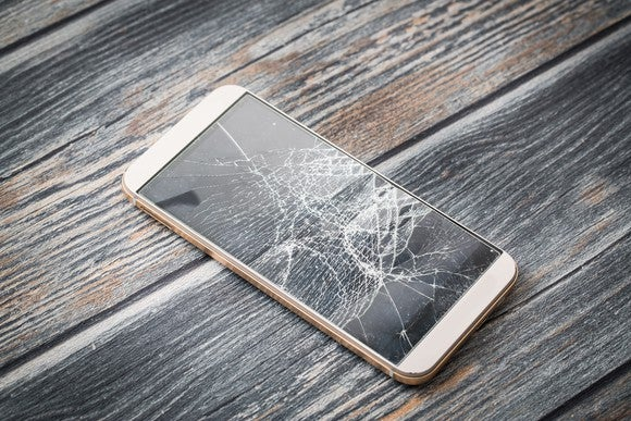 Broken smartphone sitting on table.