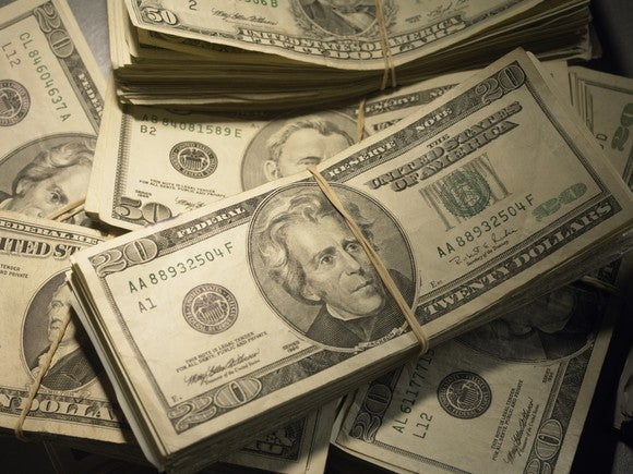 Bundles of dollar bills in different denominations bound by rubber bands.