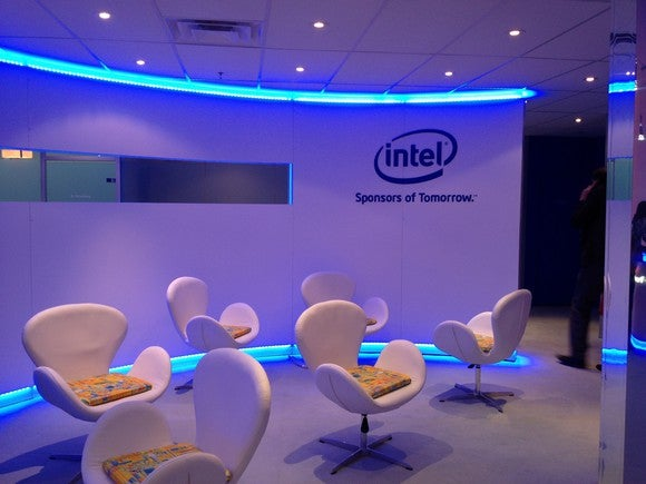 Room with six chairs and a curved wall, flanked by neon blue trim, with the Intel logo on the wall.