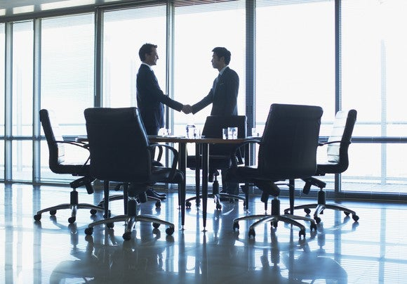 Two men shaking hands in a conference room