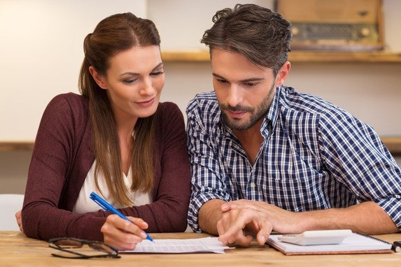 Woman writing on a piece of paper next to a man with a calculator