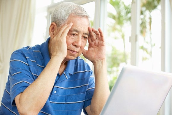 Senior man holding his head while looking at a laptop