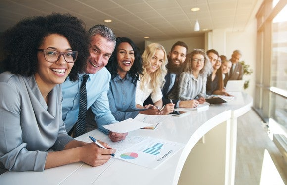 Line of smiling professionals leaning against a desk