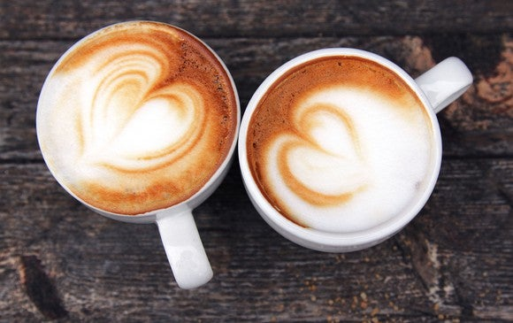 Two coffee cups seen from above, with brown and white swirled foam on the surface of the drinks.