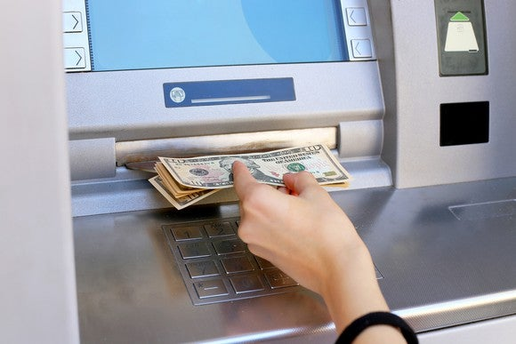 A hand pulling money out of an ATM.