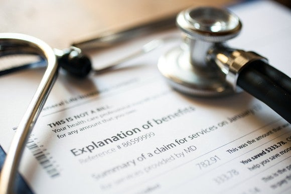 A stethoscope rests on a piece of paper that reads explanation of benefits.