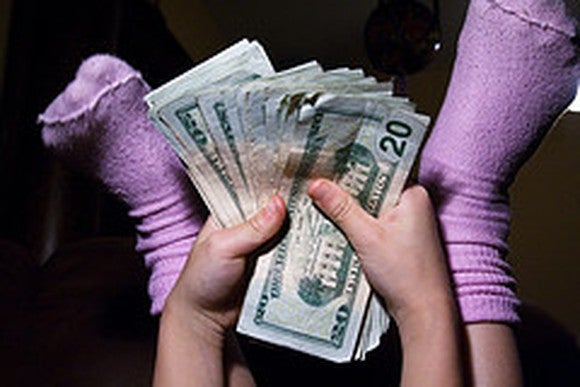 Close up picture of a persons stocking feet with handfuls of cash.