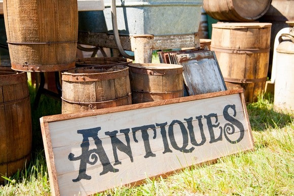 Sign with the word antiques on it, resting outdoors on the grass against a pile of wooden barrels.