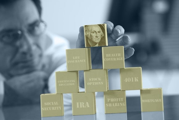 Man stacking gold colored bricks with financial tools printed on them