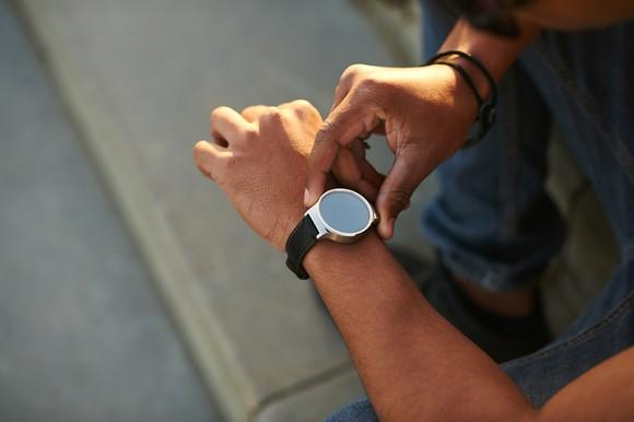 A man checks his smartwatch.