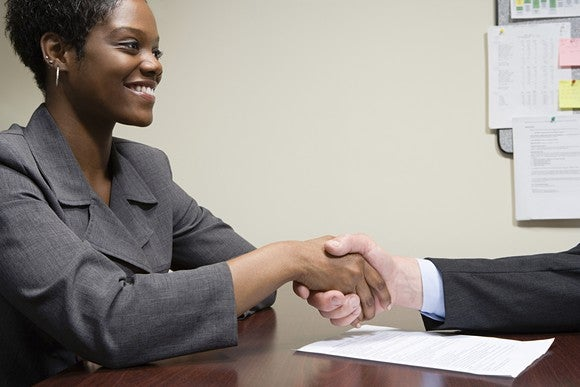 Professionally dressed woman shaking hands with another professional