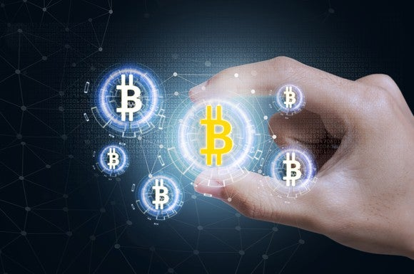 The bitcoin symbol on a digital representation of a coin floating in midair as it is being pinched by fingers