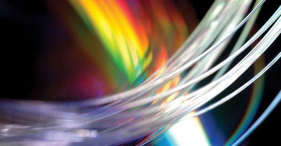 Close up shot of Corning optical fiber with rainbow-colored light in the background