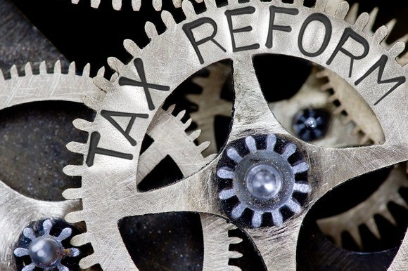 Nested gears with words Tax Reform carved on one.