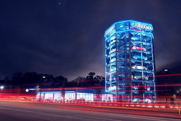 A Carvana vending machine, a glass-walled tower displaying cars, at night.