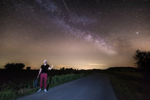 Hitchhiker pointing to Milky Way