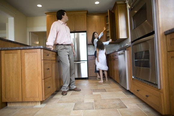 Family inspecting kitchen in house for sale