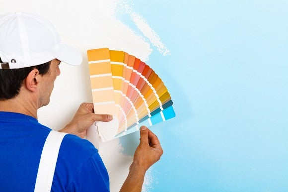 A house painter holds paint samples up to a wall.