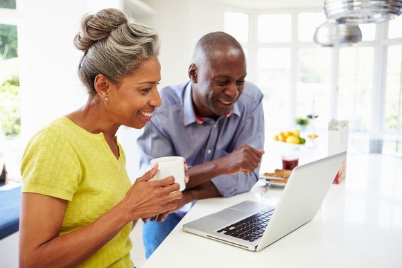 mature man and woman sitting in kitchen looking at laptop computer and smiling