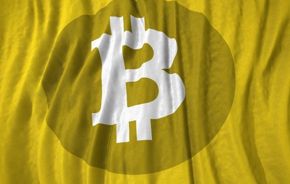 Bitcoin symbol on a yellow cloth backdrop.