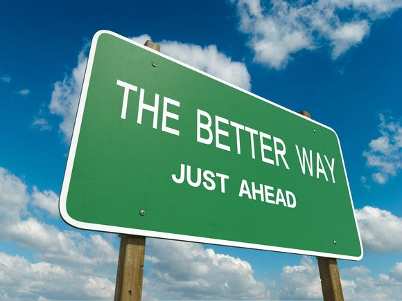 "Highway sign in front of a partially blue sky reading: ""The better way just ahead"""
