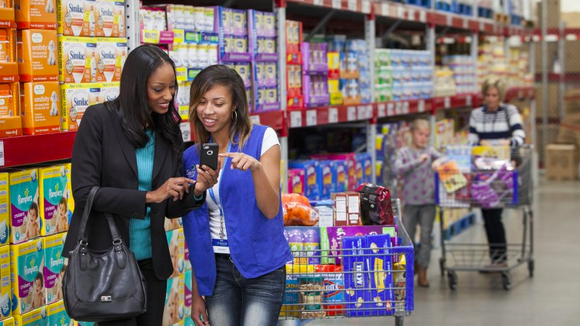 A Walmart employee helps a customer use her Walmart app whil standing in front of an aisle of baby products