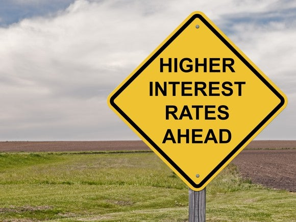 Diamond-shaped road sign that says higher interest rates ahead.