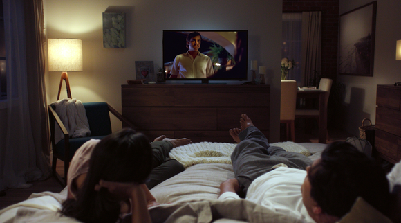 A man and a woman lie on a bed while watching a Netflix show on their TV