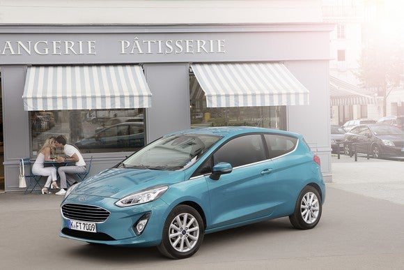 A teal 2018 Ford Fiesta hatchback in front of a French bakery.