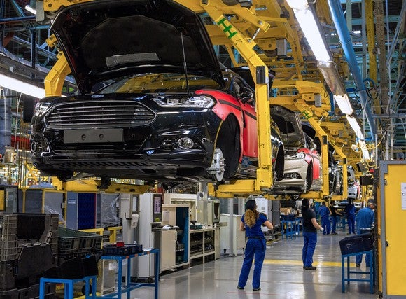 Partially-completed Mondeo sedans are shown in cradles, several feet above the factory floor, with workers underneath.