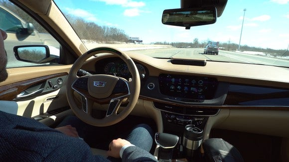 The steering wheel and dashboard of a Cadillac CT6 luxury sedan equipped with GM's Super Cruise highway driver-assist system. The driver's hands are off the steering wheel.