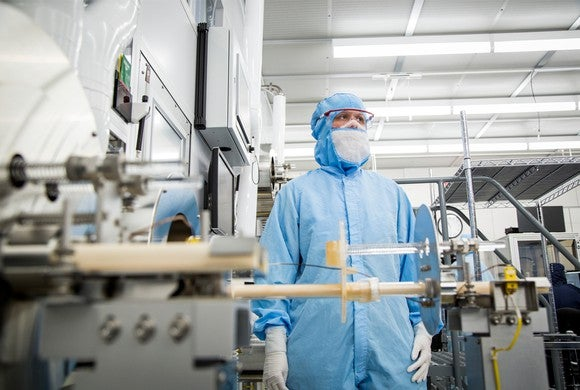 Finisar employee wearing a blue clean suit in a chip manufacturing plant
