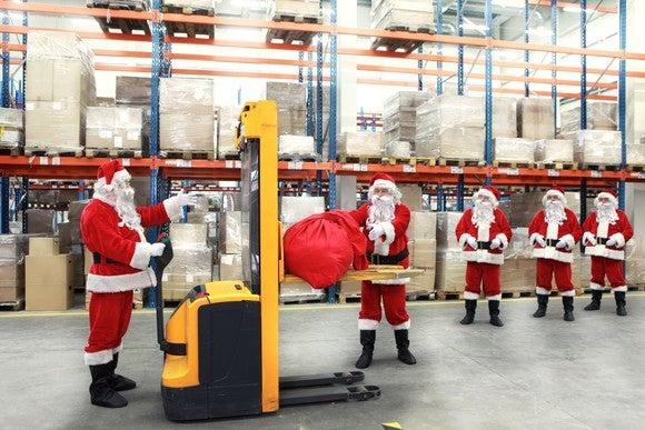 A group of Santas is shiw  in a shipping warehouse.