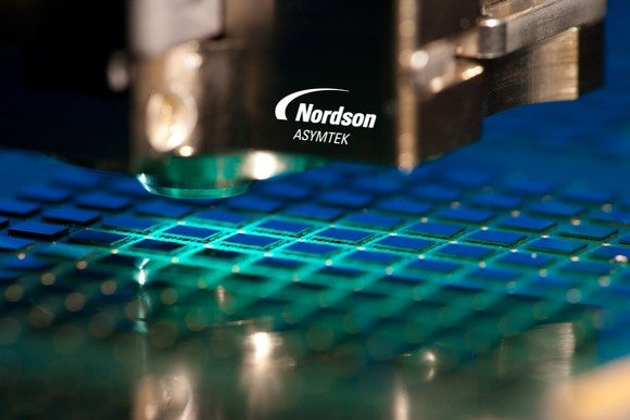 Piece of equipment labeled Nordson Asymtek helping to scan a row of semiconductor chips.