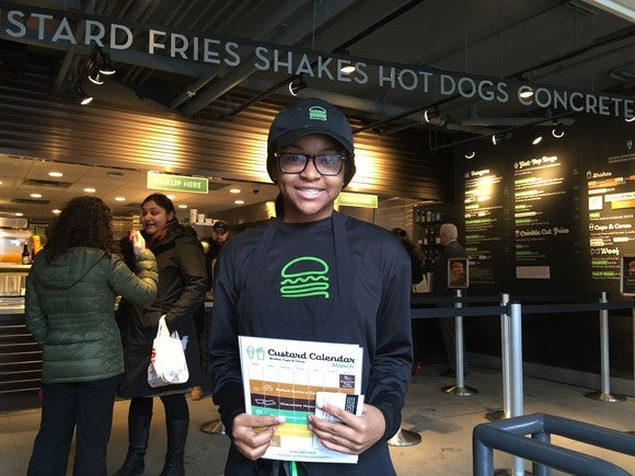 An employee greeting guests at a Shake Shack in Boston.