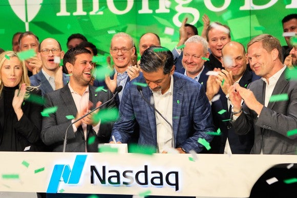 MongoDB CEO Dev Ittycheria and other members of the management team at the Nasdaq stock exchange as green confetti falls around them.