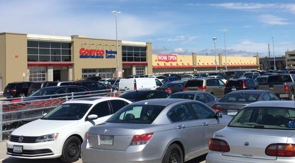 The exterior of a Costco store with a crowded parking lot.