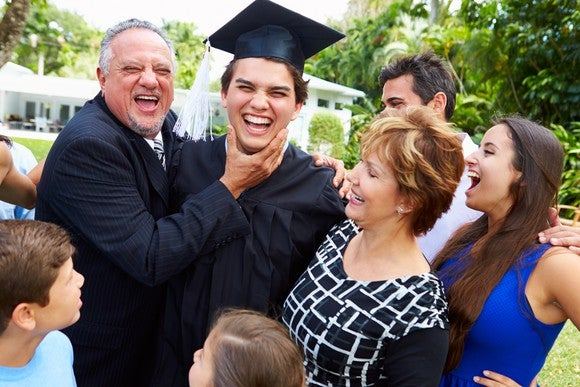 Smiling family gathered outdoors around a graduate in cap and gown.