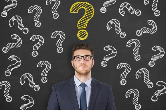 Young man in a suit stands in front of a blackboard with a bunch of question marks written in white, with one yellow question mark directly above his head.