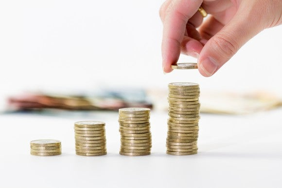 Hand building progressively larger stacks of coins. Dividend concept