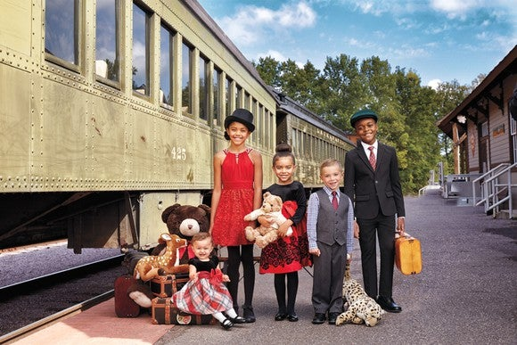 A group of children are dressed in holiday clothes in front of a train.